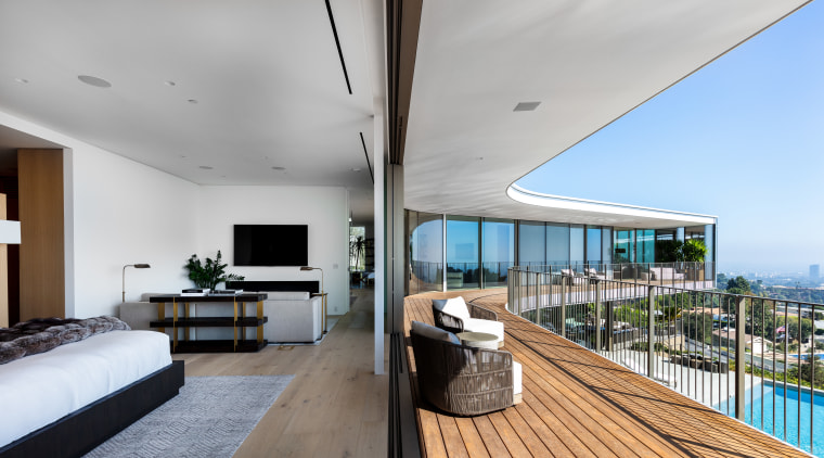 At one end of the first floor of architecture, balcony, building, ceiling, wood floor, floor, flooring, wood deck, bedroom, furniture, home, house, interior design, living room, penthouse apartment, property, real estate, roof, room, table, gray