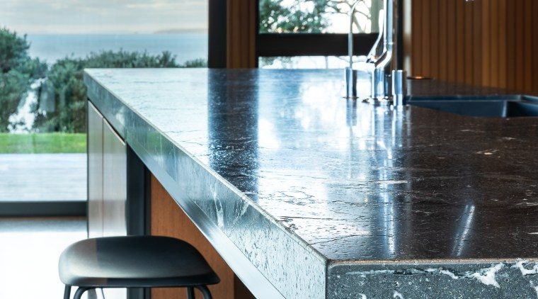 The leathered granite island benchtop adds textural interest architecture, building, cabinetry, countertop, floor, flooring, furniture, glass, granite, home, house, interior design, kitchen, marble, material property, property, room, table, tile, window, white, black