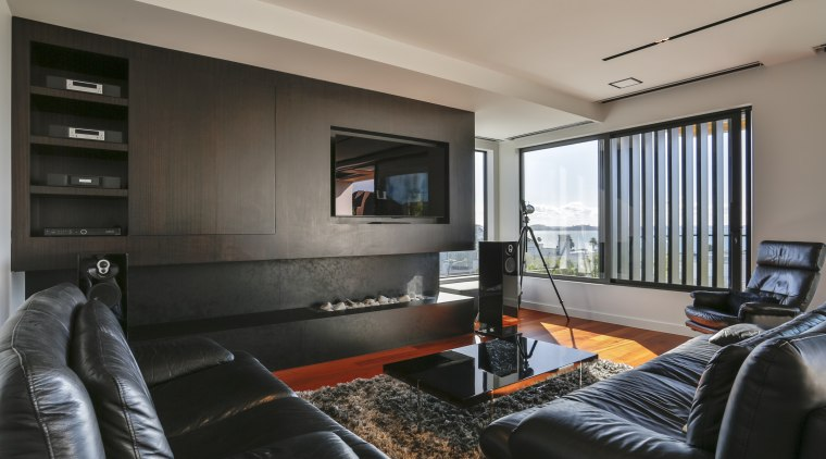 ​​​​​​​Dark living room cabinetry anchors the white, open gray, black