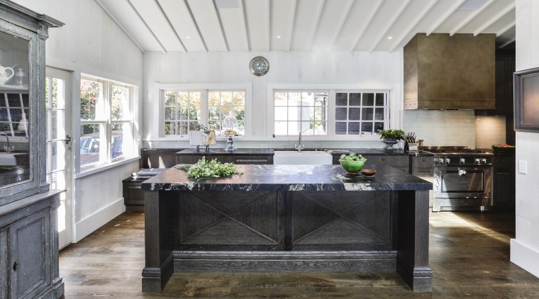​​​​​​​Elegant chocolate-stained oak cabinetry panelling and chunky leathered gray, white