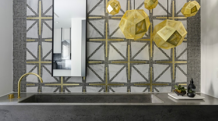 ​​​​​​​An intricately patterned, custom feature wall of brass gray, black