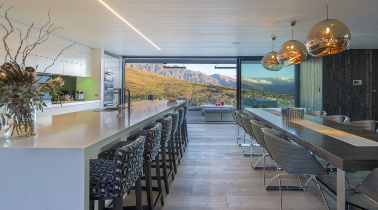 The long white, minimalist kitchen in this mountain