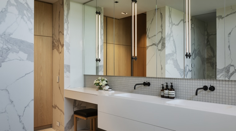 ​​​​​​​A room-length vanity is matched with mirror-front wall