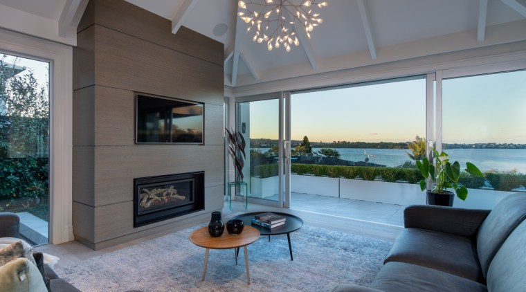 ​​​​​​​Room-high glass sliders open up this lakeside home