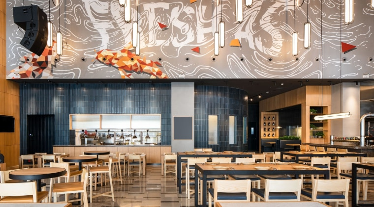 Above the open kitchen, a mural of stylised architecture, brunch, building, café, cafeteria, ceiling, coffeehouse, design, dining room, fast food restaurant, food court, furniture, interior design, lighting, restaurant, room, table, gray