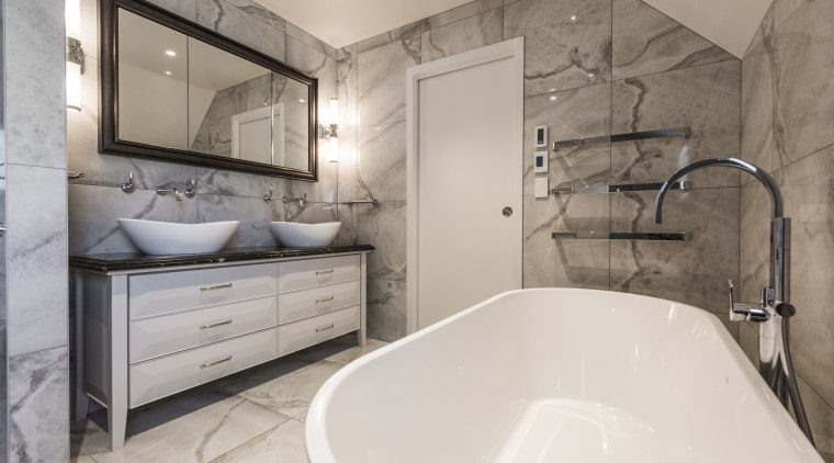 Tub and basins connect in the refined bathroom. architecture, bathroom, bathtub, building, ceiling, floor, furniture, home, house, interior design, marble, plumbing fixture, property, real estate, room, tap, tile, wall, gray