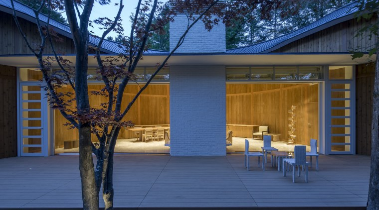 Shishi-iwa – exterior of Grand Room at dusk. architecture, building, cottage, door, facade, home, house, log cabin, property, real estate, residential area, roof, room, shed, siding, tree, window, blue