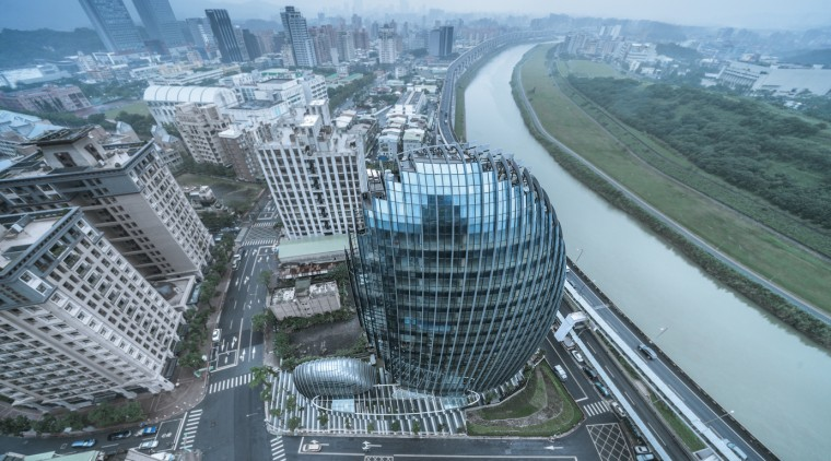 The building's egg-like shape implies it is an aerial photography, architecture, bird's-eye view, building, city, cityscape, commercial building, corporate headquarters, daytime, downtown, freeway, headquarters, human settlement, landmark, landscape, metropolis, metropolitan area, mixed-use, real estate, sky, skyline, skyscraper, tower, tower block, urban area, urban design, world, gray, teal