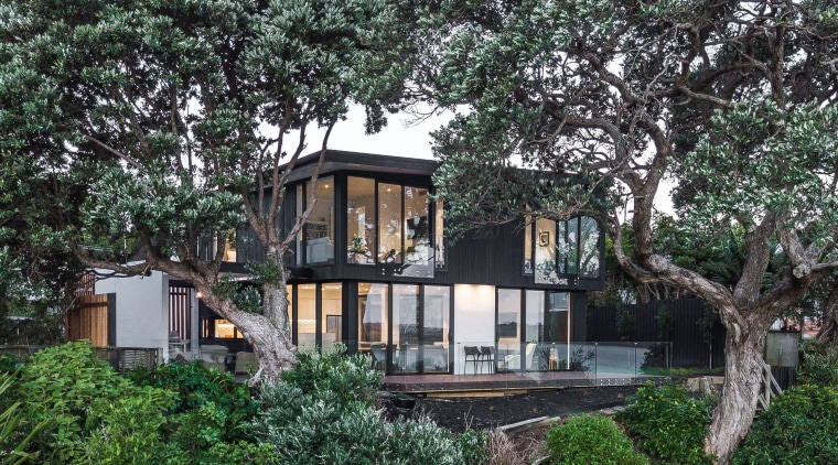 This new home in Whangaparaoa is nestled amongst architecture, cottage, estate, home, house, outdoor structure, plant, property, real estate, residential area, tree, villa, black
