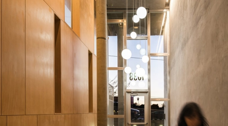 The entrance features contrasting concrete and wood architecture, ceiling, daylighting, floor, flooring, interior design, lobby, brown, orange
