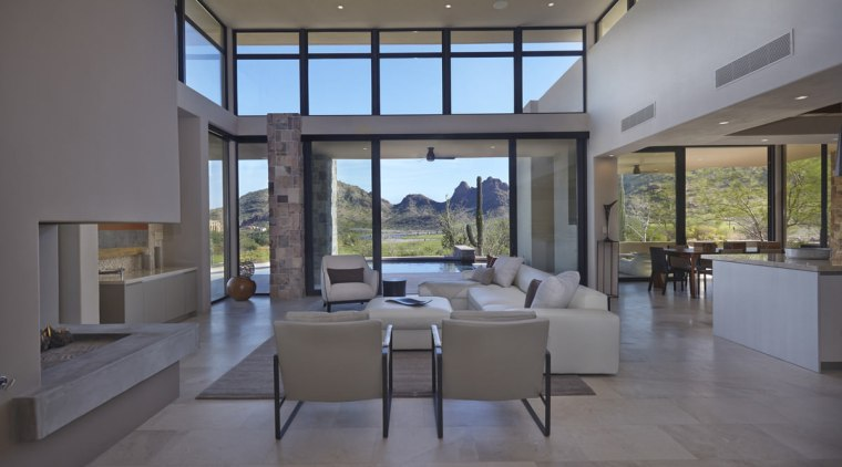 The fireplace sits off to the side of architecture, ceiling, daylighting, estate, floor, house, interior design, living room, lobby, property, real estate, window, gray