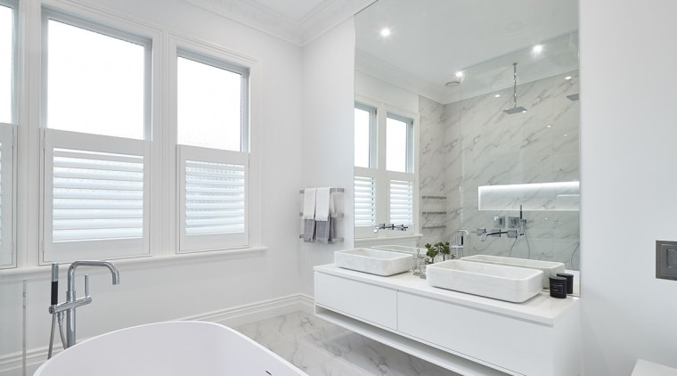 This master ensuite features a freestanding tub; his-and-hers architecture, bathroom, floor, home, interior design, real estate, room, sink, window, white, gray