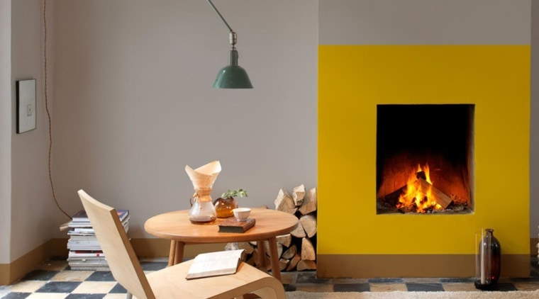What could have been a forgettable fireplace was fireplace, furniture, hearth, heat, home, interior design, living room, orange, room, table, wood-burning stove, gray