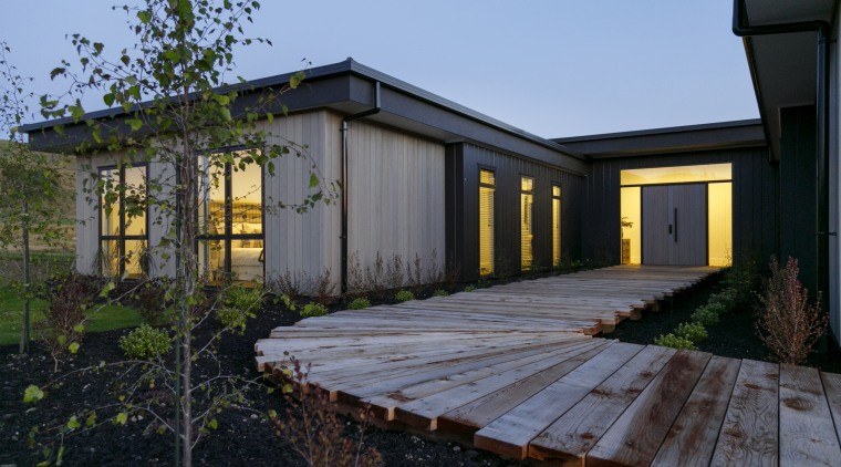 A timber boardwalk leads to a solid front architecture, backyard, building, cottage, estate, facade, home, house, landscape, property, real estate, residential area, roof, shed, siding, tree, window, wood, yard, black