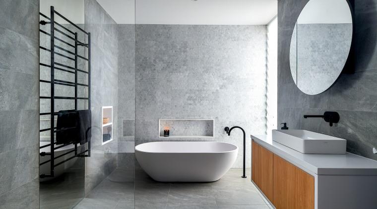 Natural-look materials, a freestanding tub, a cantilevered vanity architecture, bathroom, bathtub, bidet, building, ceramic, floor, flooring, house, interior design, material property, plumbing fixture, property, room, tap, tile, wall, gray