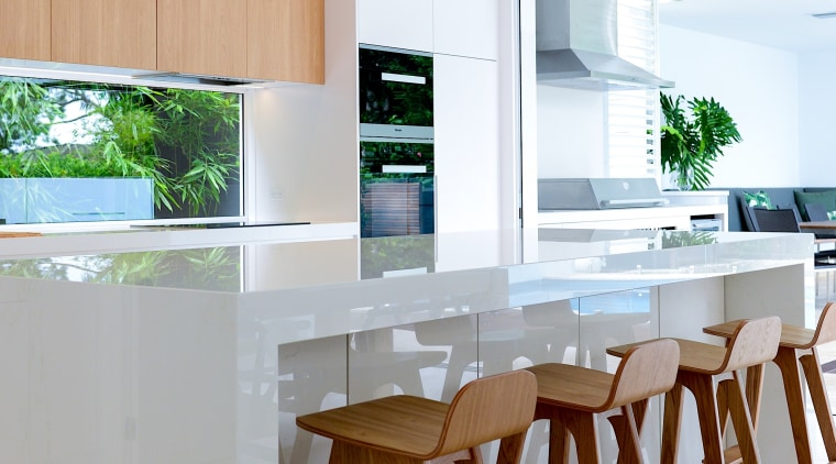An extended waterfall countertop provides breakfasters with leg architecture, bar stool, building, cabinetry, ceiling, countertop, dining room, floor, flooring, furniture, hardwood, home, house, interior design, kitchen, material property, property, real estate, room, stool, table, white, gray