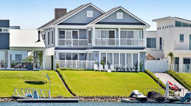 At the rear of this Hampton's style home, apartment, architecture, boating, building, estate, home, house, leisure, mansion, property, real estate, residential area, roof, vacation, vehicle, villa, water transportation, waterway, teal