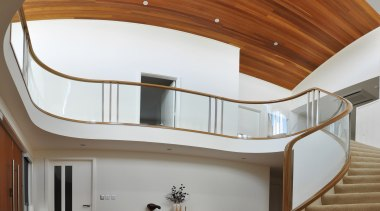 A curvaceous glass balustrade framed in wood by architecture, ceiling, daylighting, furniture, handrail, home, house, interior design, product design, property, stairs, brown, gray
