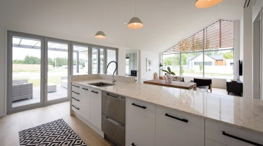 A soaring raked ceiling and expansive window wall cabinetry, countertop, cuisine classique, home, interior design, kitchen, real estate, room, window, gray