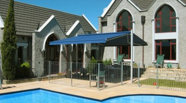 The stylish Plaza Outdoor Canopy provides excellent sun backyard, elevation, estate, facade, home, house, leisure, outdoor structure, property, real estate, residential area, shade, siding, swimming pool, window, teal