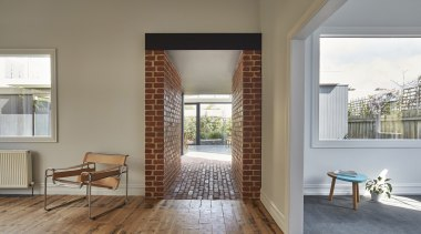 The brick 'tunnel' connects the new and the door, floor, flooring, home, house, interior design, real estate, window, window covering, window treatment, wood, gray