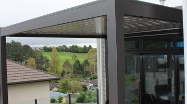 The new roof is two-tone, including a light outdoor structure, patio, pergola, white, black