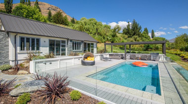 The word 'relax' comes to mind with this backyard, cottage, estate, home, house, landscape, leisure, property, real estate, residential area, swimming pool, villa, yard, gray