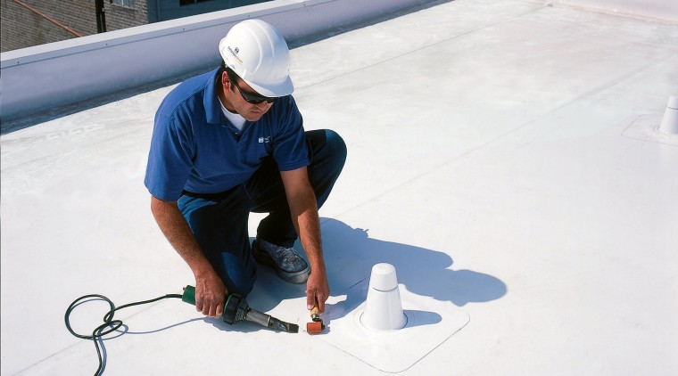 workman on roof of townhouse complex floor, flooring, material, roof, water, white