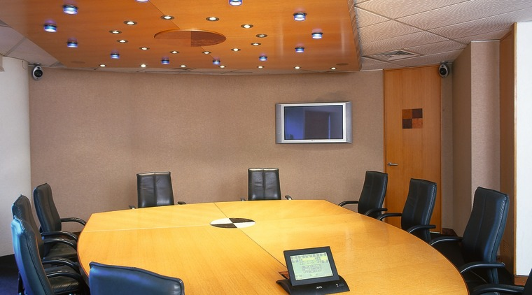 board table with laptop and wall mounted tv auditorium, ceiling, conference hall, interior design, office, table, brown
