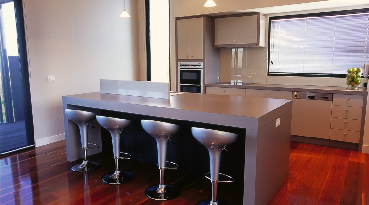 Neutral coloured kitchen with four stools at kitchen cabinetry, countertop, desk, floor, flooring, furniture, hardwood, interior design, kitchen, laminate flooring, real estate, room, table, wood, wood flooring, red, gray