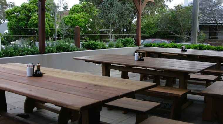 Outdoor paved eating area with timber tables and furniture, outdoor furniture, outdoor structure, patio, pavilion, table, black