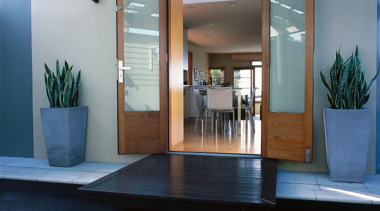 This kitchen has an opening to an ornamental door, floor, glass, house, interior design, window, black, gray