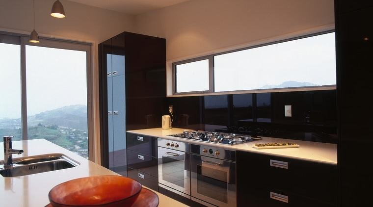 Kitchen with stainless steel ovens and gas cooktop, countertop, interior design, kitchen, real estate, black, brown