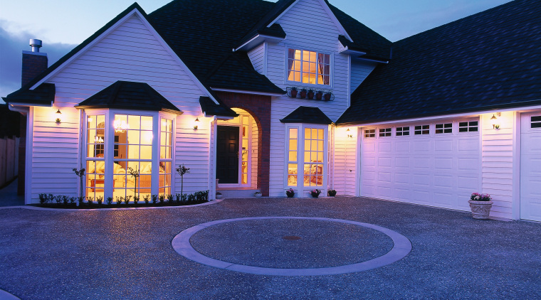 A photograph of a two storey house featuring architecture, building, cottage, estate, evening, facade, home, house, landscape lighting, lighting, property, real estate, residential area, roof, shed, siding, sky, suburb, window, blue