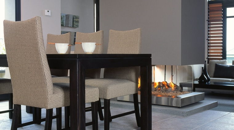A photograph of a dining area featuring a chair, coffee table, dining room, fireplace, floor, flooring, furniture, hearth, interior design, living room, table, wood burning stove, gray, black