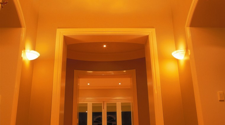 A photograph of a well lighted hallway featuring architecture, ceiling, column, daylighting, estate, flooring, function hall, hall, home, house, interior design, light, light fixture, lighting, lobby, property, room, wall, brown, orange