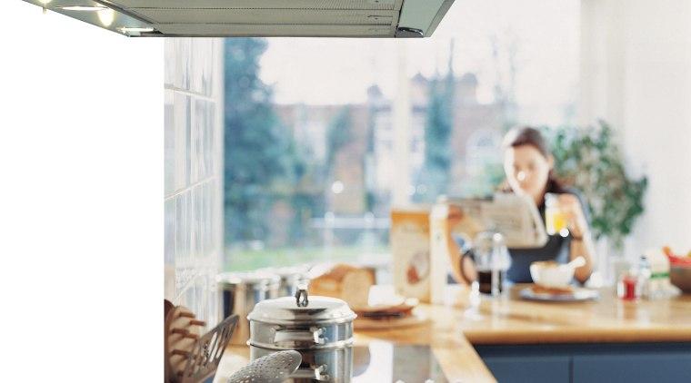 Kitchen showing rangehood mounted over kitchen island, with furniture, interior design, kitchen, kitchen appliance, table, white