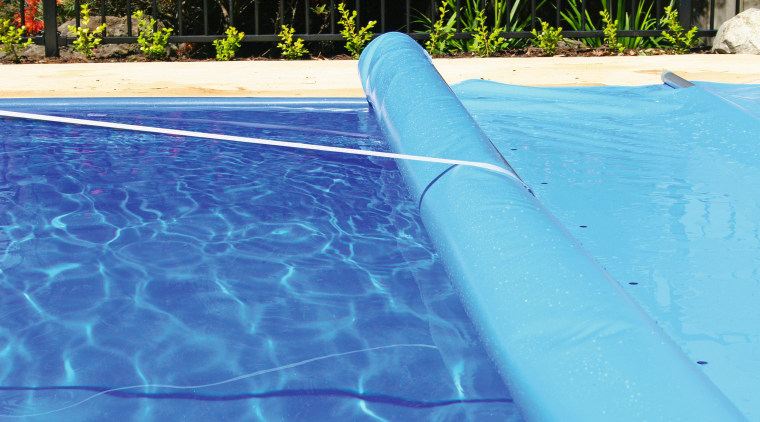 Swimming pool with blue cover being rolled up. azure, blue, leisure, swimming pool, water, teal, blue