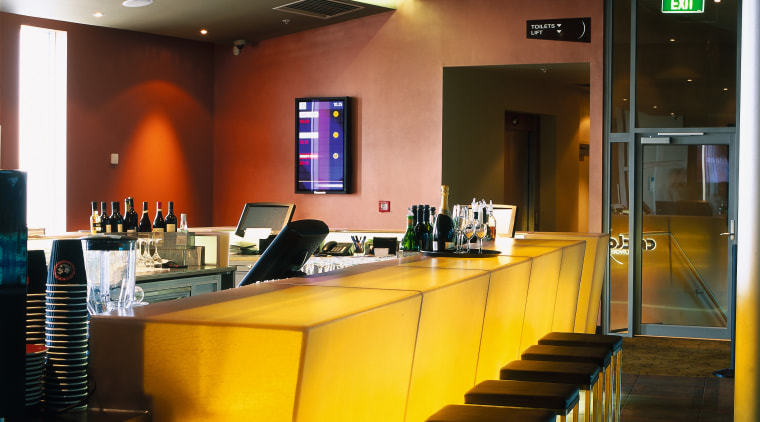 Bar area of cinema complex with yellow bar interior design, lighting, restaurant, table, brown