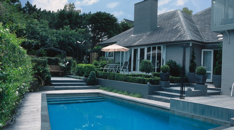 Outdoor pool and patio area featuring grey paving backyard, cottage, estate, home, house, leisure, outdoor structure, property, real estate, residential area, resort, roof, sky, swimming pool, villa, water, teal
