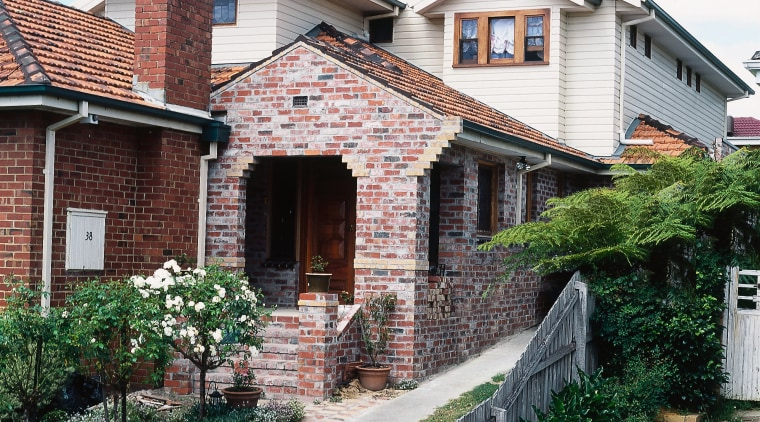 Exterior of home with brick cladding in front building, cottage, estate, facade, home, house, neighbourhood, property, real estate, residential area, roof, siding, suburb, villa, window, white