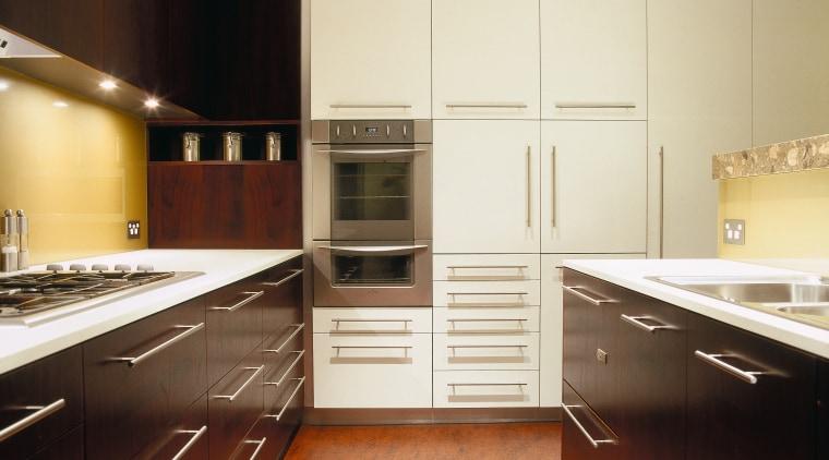 view of the kitchen showing dark stained american cabinetry, countertop, cuisine classique, floor, flooring, hardwood, interior design, kitchen, room, under cabinet lighting, wood flooring, yellow