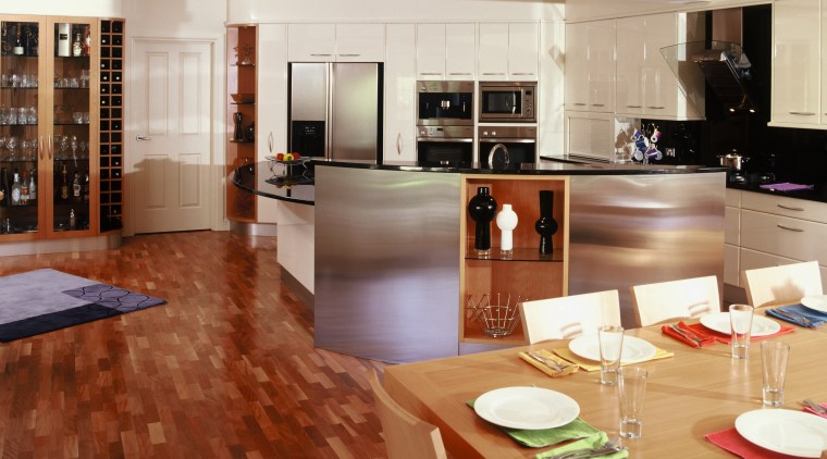 View of kitchen and dining area featuring parquetry countertop, floor, flooring, hardwood, interior design, kitchen, laminate flooring, room, wood, wood flooring
