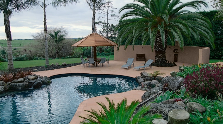 view of this lush outdoor living/pool area featuring arecales, backyard, estate, hacienda, home, landscape, landscaping, leisure, outdoor structure, palm tree, plant, property, real estate, resort, swimming pool, tree, water feature, yard, gray