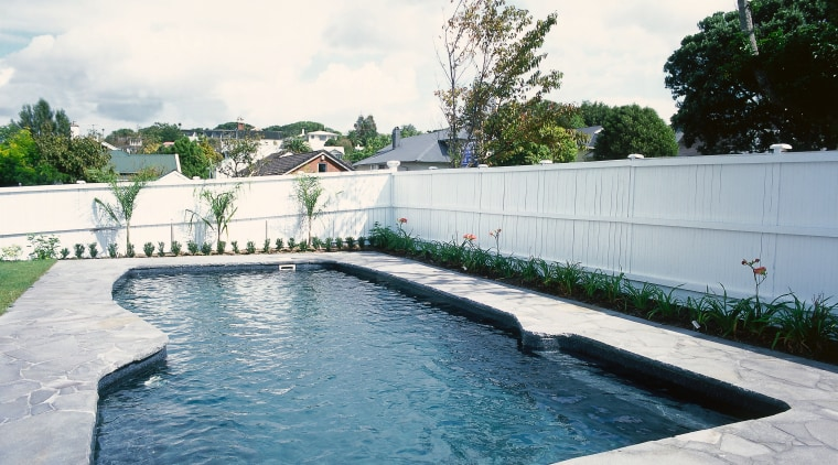 A view of a swimming pool. backyard, estate, fence, leisure, outdoor structure, property, real estate, swimming pool, wall, water, white, gray