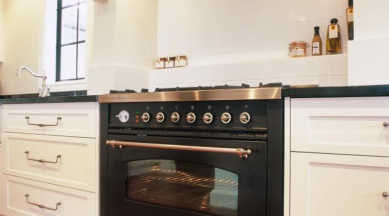 View of black oven set in cream kitchen cabinetry, countertop, cuisine classique, floor, flooring, home appliance, interior design, kitchen, kitchen appliance, kitchen stove, major appliance, oven, room, white