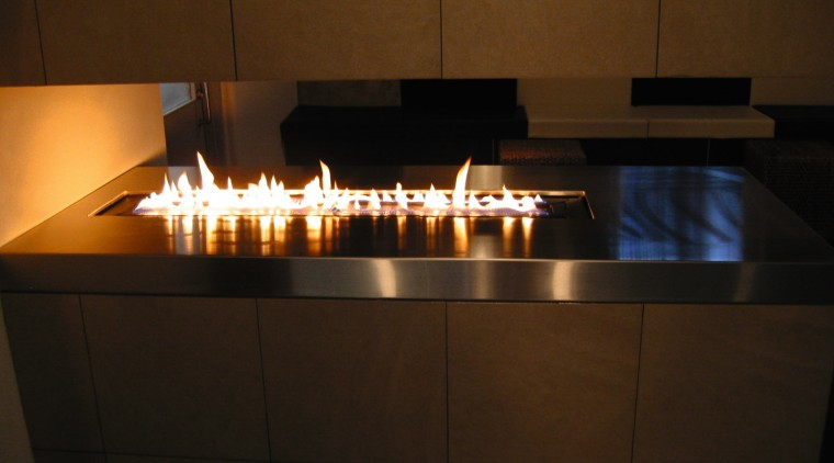 Gas burner fireplace feature. fireplace, hearth, heat, light, lighting, table, brown, black