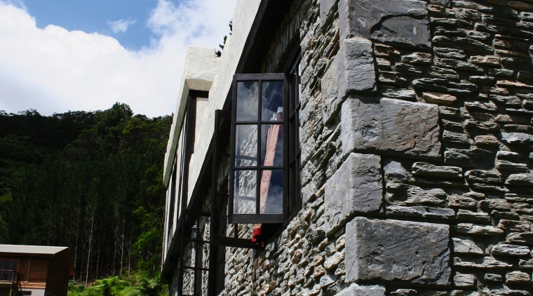 View of exterior of home clad in stone. building, cottage, facade, house, sky, stone wall, wall, window, black, gray
