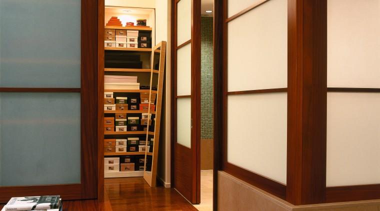 view of this master bedroom leading to the bookcase, cabinetry, door, floor, flooring, furniture, interior design, shelf, shelving, brown, orange