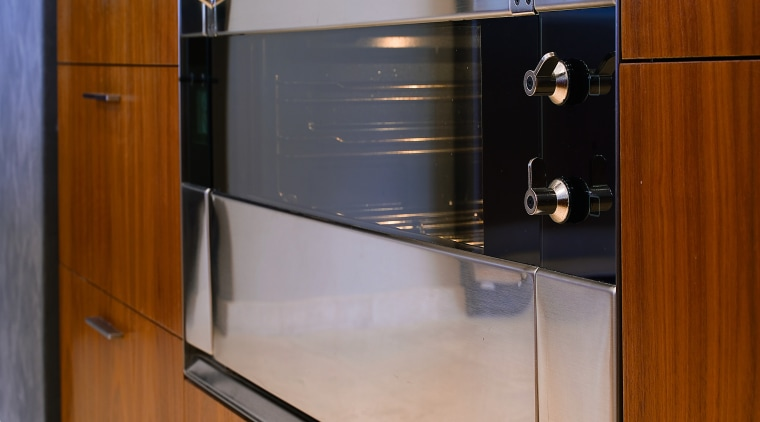 Closeup view of stainless steel oven set into cabinetry, countertop, furniture, home appliance, kitchen, major appliance, gray, brown